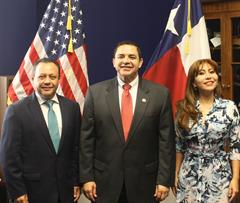 Congressman Henry Cuellar stands and smiles between Mexican Congressman Braulio Guerra and Mexican Congresswoman Liliana Oropeza, in front of the flags of the United States and Texas.